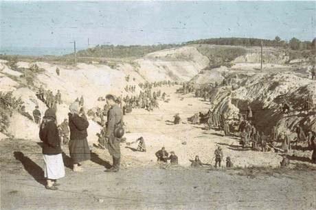На допросе бывший пленный Б.В. Соколов признал, что в октябре 1941 года более 300 военнопленных были отправлены в овраг Бабий Яр закапывать тела расстрелянных. На фото они на уровне земли над массой песка. Немецкий солдат показывает украинским женщинам рабочих в овраге.